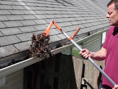 man using tool to clean gutter