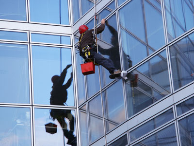 man suspended from building cleaning windows