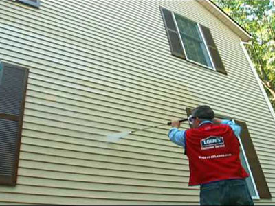 man pressure washing siding on house