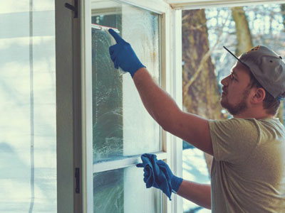 man cleaning exterior window